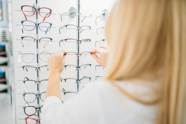 Kobieta optometrysta pokazuje okulary w sklepie optycznym