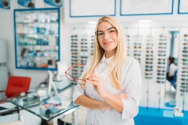 Kobieta optometrysta trzyma w rękach okulary, gablota z okularami w sklepie optycznym. dobór okularów z profesjonalnym optykiem
