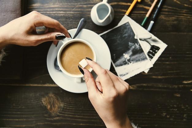 Kobieta opuszcza cukier w filiżance kawy