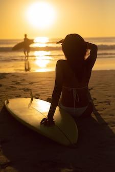 Kobieta osłania oczy z deską surfingową podczas gdy relaksujący na plaży