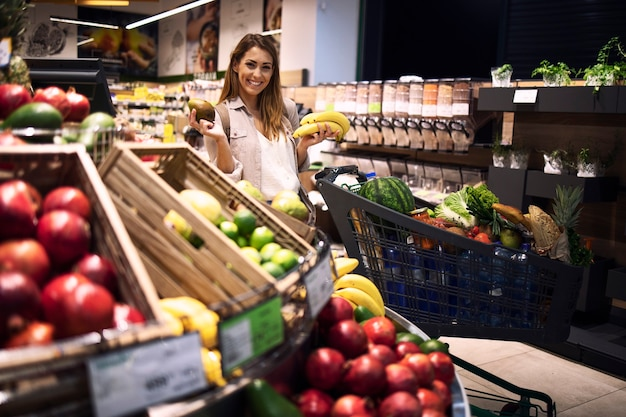 Kobieta osoba posiadająca owoce w supermarkecie i uśmiechnięta.