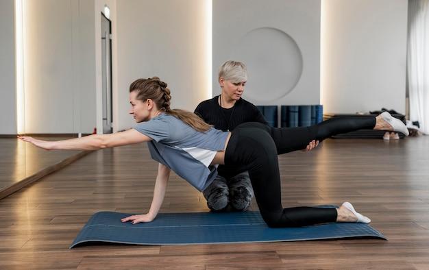 Kobieta osobisty trener pomaga jej klientowi długi widok