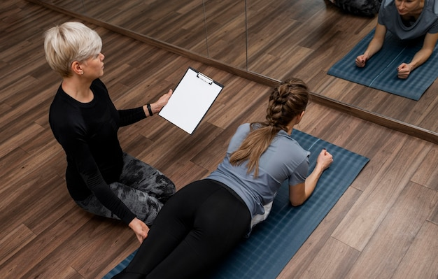 Kobieta osobisty trener pomaga jej klientowi wysoki widok