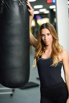 Kobieta osobisty trener z workiem treningowym w siłowni