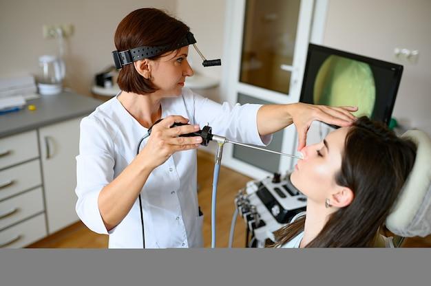 Kobieta otolaryngolog i pacjent w gabinecie, egzamin. badanie nosa w poradni, profesjonalna diagnostyka, lekarz. lekarz specjalista i kobieta w szpitalu, laryngolog