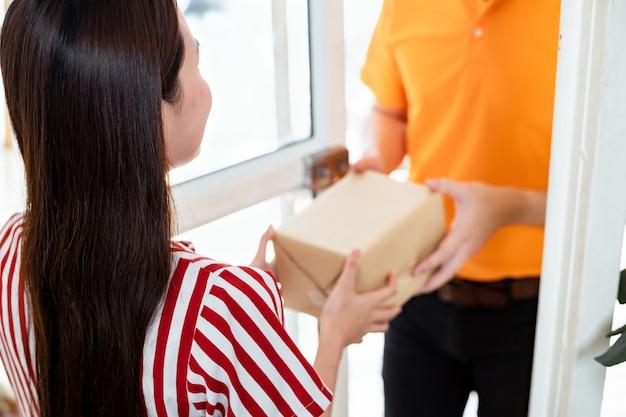 Kobieta otrzymała paczkę od listonosza w domu.