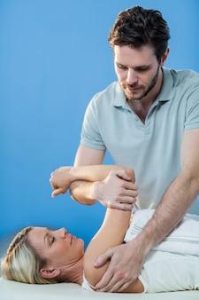 Kobieta otrzymująca terapia ramion od fizjoterapeuty