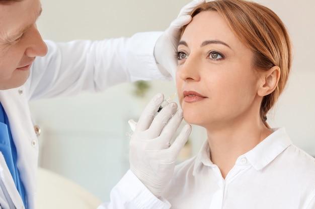 Kobieta otrzymująca zastrzyk wypełniacza w gabinecie kosmetycznym