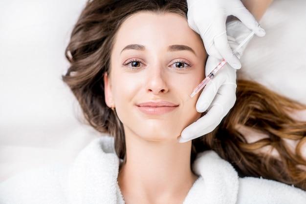 Kobieta otrzymująca zastrzyk z botoksu w okolicy ust leżąca na kanapie lekarskiej