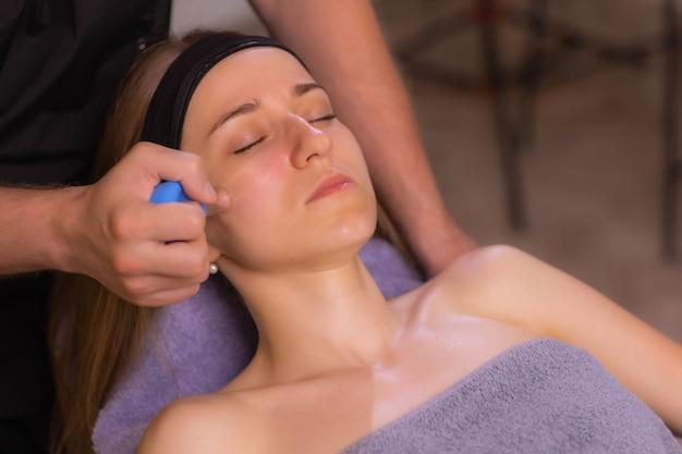 Kobieta otrzymuje masaż bańkami twarzy odmładzanie twarzy w spa akupunktury.