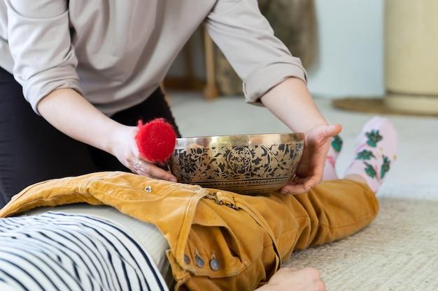 Kobieta otrzymuje masaż tybetański misą śpiewu i terapię dźwiękiem z tradycyjnej nepalskiej praktyki medycznej