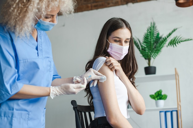 Kobieta otrzymuje szczepionkę od lekarza podczas kampanii szczepień, pandemii grypy i leczenia medycznego...