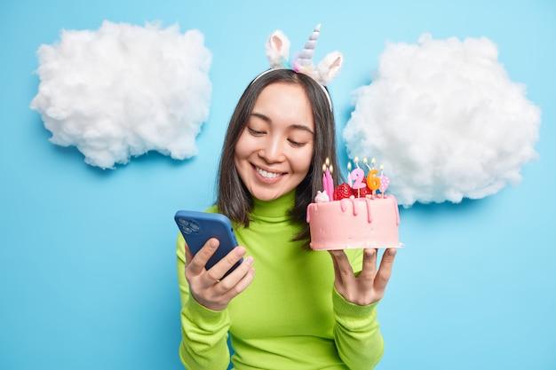 Kobieta otrzymuje wiadomość z gratulacjami na komórce wysyła informację zwrotną trzyma pyszny tort urodzinowy z płonącymi świeczkami