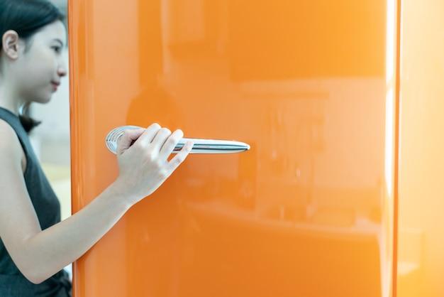 Kobieta otwarte drzwi lodówki w kuchni