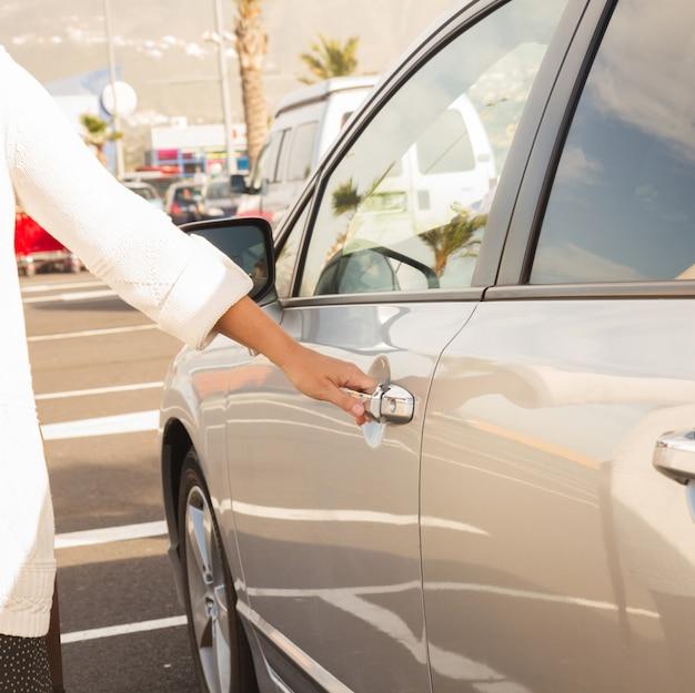 Kobieta otwiera drzwi szarego metalowego samochodu