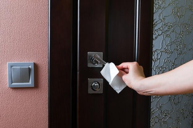 Kobieta otwiera drzwi w lateksowych rękawiczkach ochronnych. koncepcja środków rozprzestrzeniania koronawirusa.