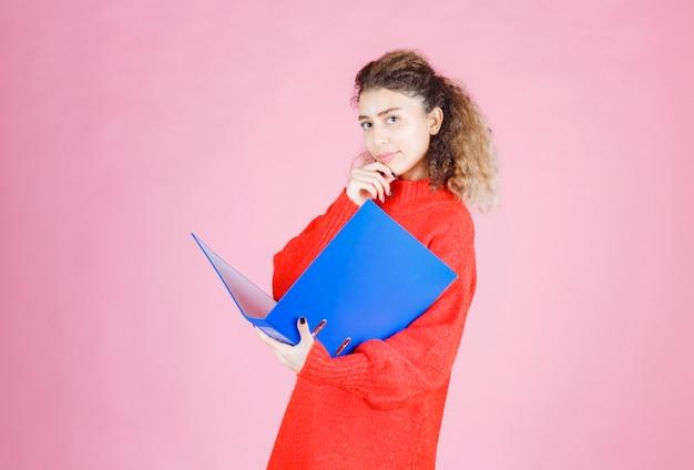 Kobieta otwiera niebieski folder raportu i wygląda na zamyśloną.