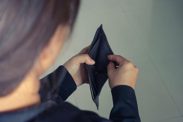 Kobieta otwiera portfel bez pieniędzy
