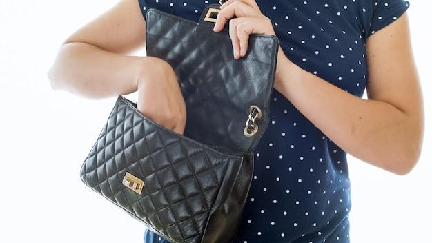 Kobieta otwiera swoją czarną skórzaną torebkę i wyjmuje rzeczy.