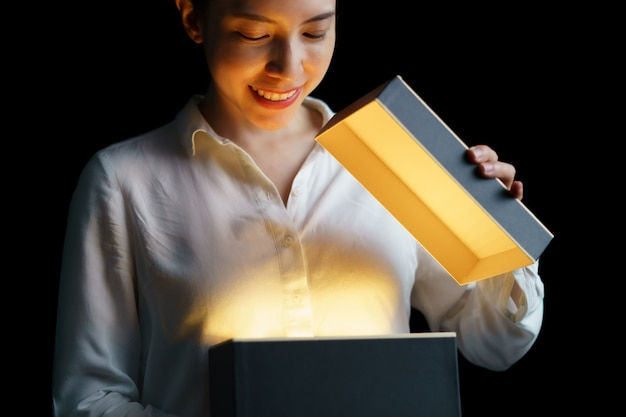 Kobieta otwierająca pudełko ze złotym światłem w środku