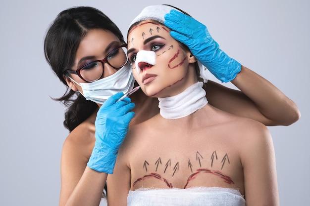 Kobieta owinięta bandażami i bliznami przygotowywana jest do kolejnej operacji.
