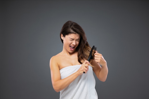 Kobieta owinięta białym ręcznikiem wokół ciała staje przed szarą ścianą i po kąpieli używa grzebienia do włosów