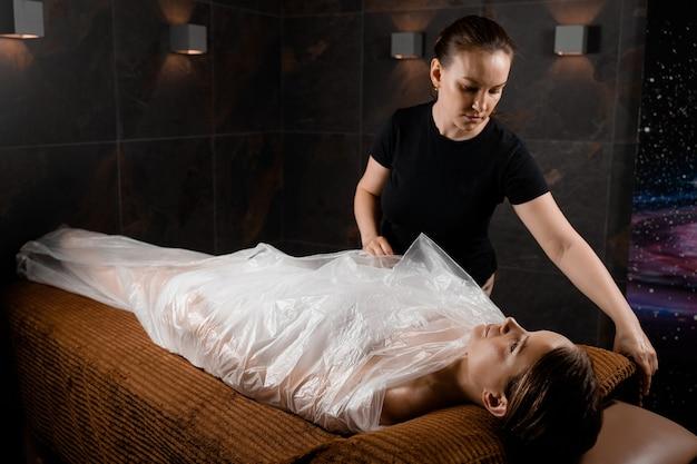 Kobieta owinięta folią polietylenową. terapia czekoladowego spa.