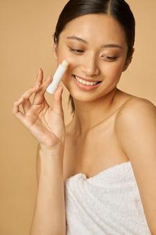 Kobieta owinięta ręcznikiem uśmiechnięta i trzymająca balsam do ust