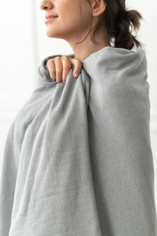 Kobieta owinięta szarym kocem zimą