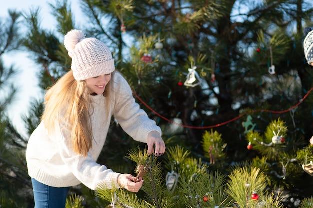 Kobieta ozdabia dekoracyjnymi zabawkami i girlandami zielone drzewo sylwestrowe na ulicy w zimie w lesie. ozdoby na choinkę