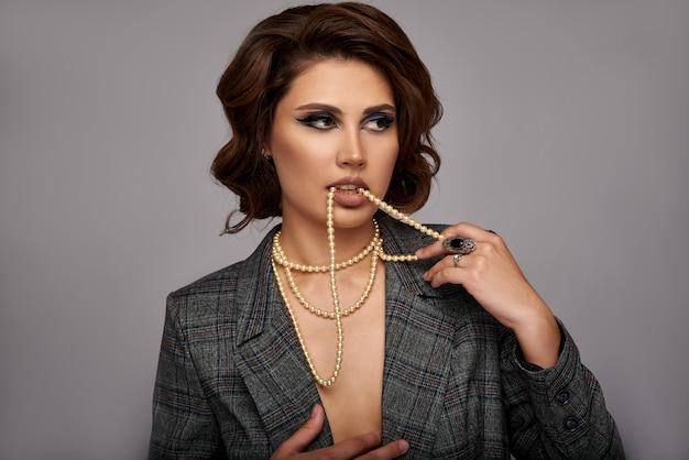 Kobieta ozdobiona perłami. biżuteria na szyi i rękach, palcach. na szarej ścianie w kurtce. koncepcja sklepów jubilerskich.