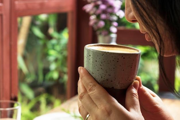 Kobieta pachnący smacznie filiżankę kawy