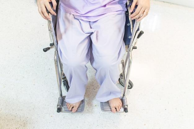Kobieta pacjent w wózka inwalidzkiego obsiadaniu w szpitalnym korytarzu