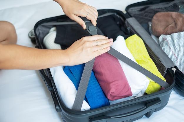 Kobieta pakowania bagażu na łóżku