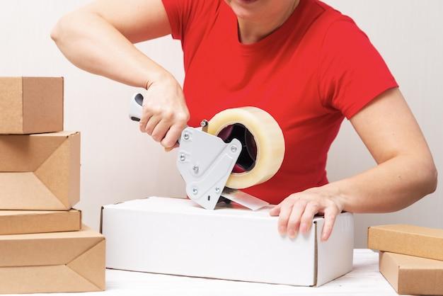 Kobieta pakowania kartonów za pomocą dozownika taśmy