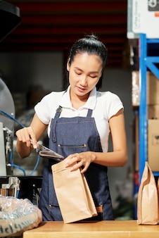 Kobieta pakowania ziaren kawy w fabryce