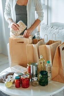 Kobieta pakująca jedzenie do darowizny w papierowej torbie