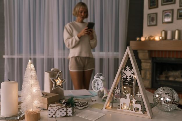 Kobieta pakująca prezenty świąteczne, pakująca prezenty na boże narodzenie i nowy rok. dekorowanie świątecznych pudełek na prezenty. przygotowanie do bożego narodzenia. ferie zimowe, koncepcja dekoracji domu
