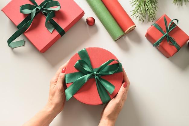 Kobieta pakująca pudełka na prezenty na boże narodzenie w czerwony i zielony papier do pakowania na święta. widok z góry. transparent.