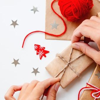 Kobieta pakuje świąteczne i noworoczne prezenty diy w papier rzemieślniczy