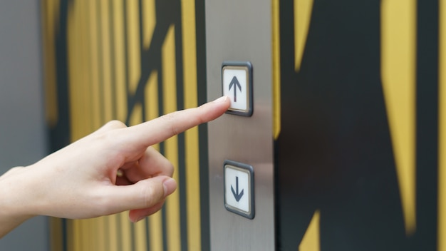 Kobieta palec naciska up guzika winda guzik w budynku.