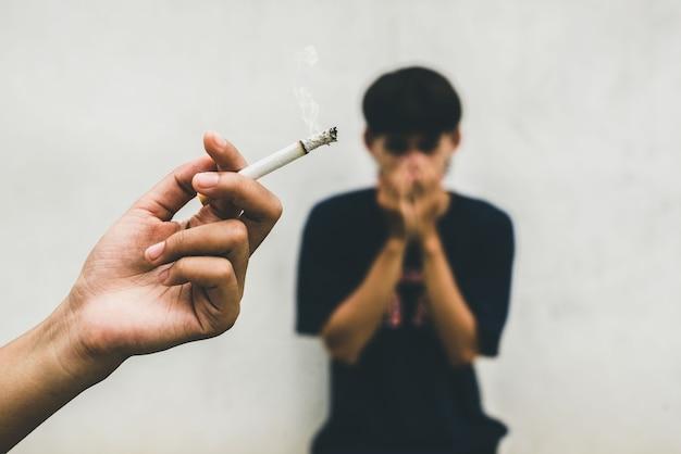 Kobieta pali papierosa, a mężczyzna zakrywa twarz. bierne palenie i opieka zdrowotna lub koncepcja dnia bez tytoniu.