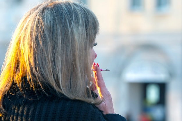 Kobieta pali papierosa na ulicy. zły nawyk.