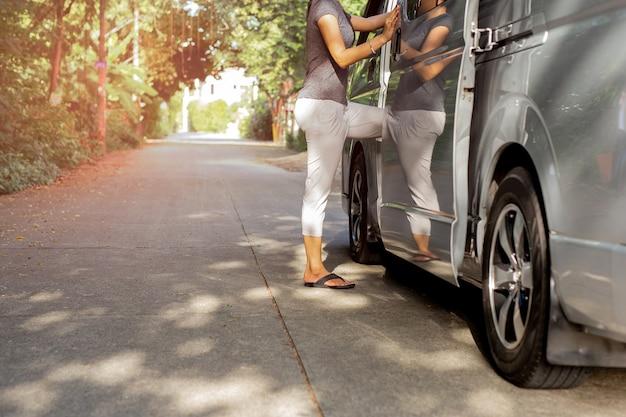 Kobieta pasażer jest ubranym trzepnięcie klapy dostaje na autobusie
