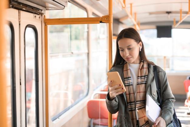 Kobieta pasażer opierając się na słupie tramwajowym