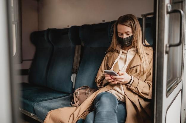 Kobieta pasażer siedzi w pociągu i ma na sobie maskę medyczną