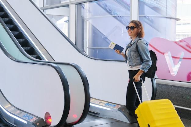 Kobieta pasażer w terminalu lotniska z bagażem, walizką i plecakiem