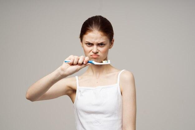 Kobieta pasta do zębów szczotkowanie zębów dentystyczne zdrowie na białym tle