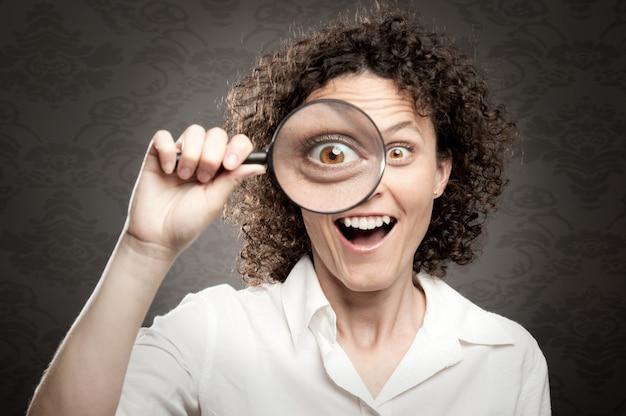 Kobieta, patrząc na kamery przez szkło powiększające