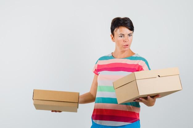 Kobieta patrząc na kartony w t-shirt w paski i wyglądająca na zdezorientowaną.